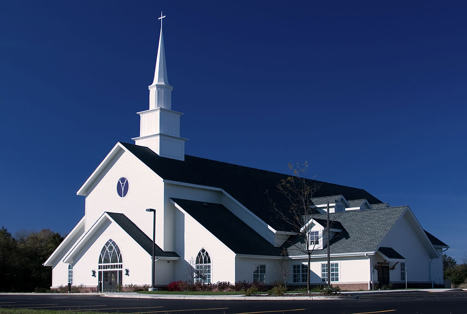 Large, white church with black roof. An all white peak is topped by a cross