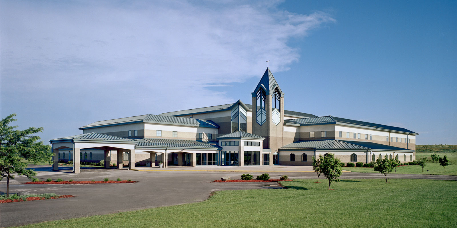 Expansive church with a large modern stoop in the center. A bright blue roof flows over the building and adjoining carport