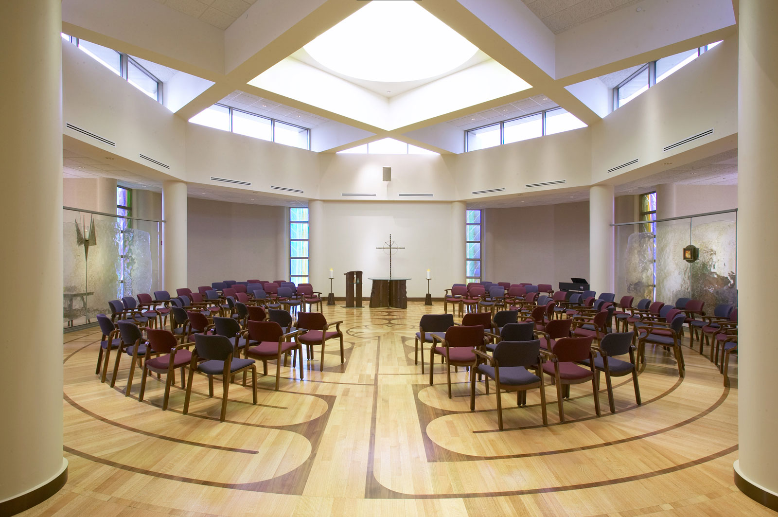 Large open room with standing chairs arranged in rows, They're centered around and facing the center podium