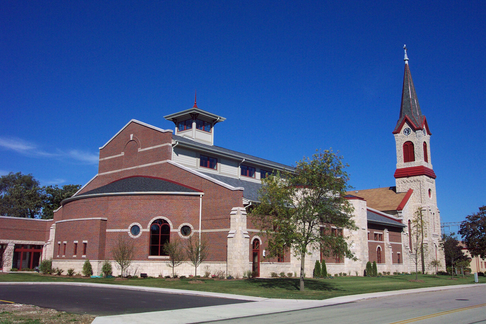 Red brick church with tan stone pillars running along side. One end has a large steeple, while he other holds the nave